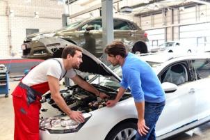 Automechaniker im Beratungsgespräch mit Kunden